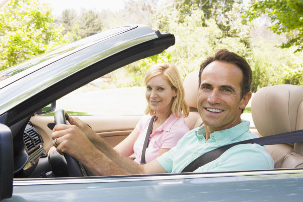 man and woman in convertible automobile